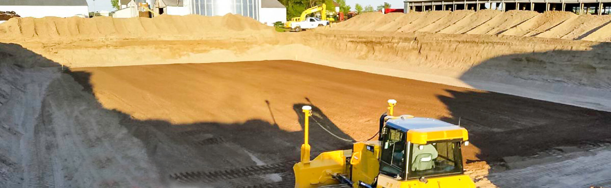 Yellow Dozer overlooking a freshly excavated building pad for agricultural construction