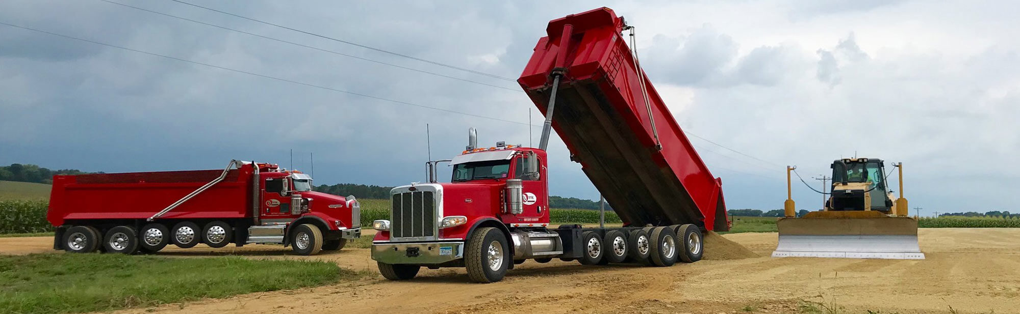 Red Otte Excavating dump truck pouring fresh aggregate at an excavating site